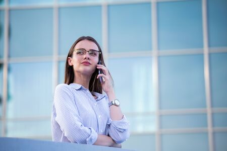 Executive business woman looking at mobile smartphone in the street with office buildings in the background.