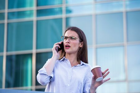 Business woman recieving bad news on smartphone and drinking coffee from disposable paper cup in the street with office buildings in the background.