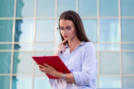 Executive business woman with clipboard against the urban background