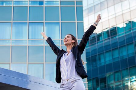businesswoman in a business suit, exulted by happiness after finishing the deal, in the background skyscrapers. Concept of: business, technology, economy and work and success. Imagens