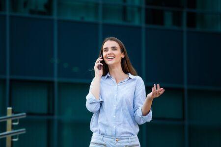 Glücklich lächelnde Geschäftsfrau, die auf dem Handy auf der Straße mit Bürogebäuden im Hintergrund spricht.
