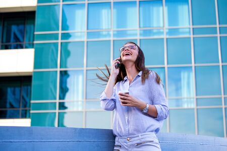 Happy smiling business woman talking on mobile smartphone and drinking coffee from disposable paper cup in the street with office buildings in the background.