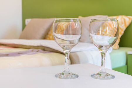 Two half full or half-empty wine glasses on night table next to the double bed in modern hotel bedroom. Valentines day or anniversary concept. Close up. Banque d'images