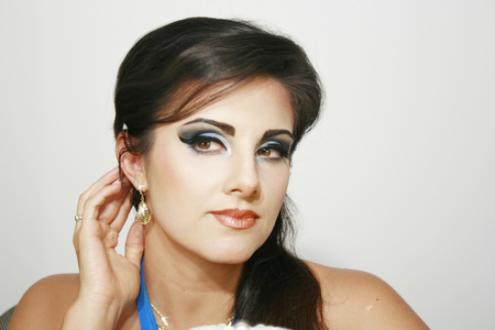 eyemakeup: Beautiful girl with blue intense makeup and earings, with long dark hair