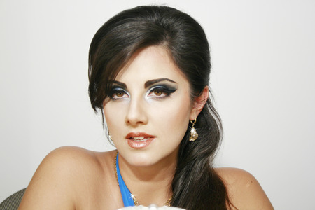 eyemakeup: Beautiful girl with romantic  look, blue intense makeup and earings, with long dark hair