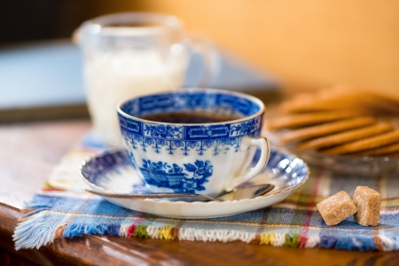 Vintage coffee cup with gingerbread cookies, milk and sugar on a tablecloth, shallow depth of field photo