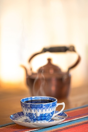 Vintage blue coffee cup with a copper kettle in background, smoking hot coffee Stock Photo - 15325349