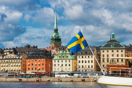 背景、ストックホルムの旧市街とスウェーデンの国旗 写真素材
