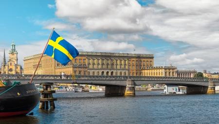 schweden flagge: Schwedische Flagge mit dem k�niglichen Schloss im Hintergrund, Stockholm