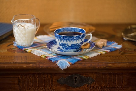Blue coffee cup with milk on a wooden table, ginger cakes in the back