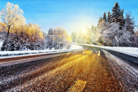 Winter road with sunlight reflecting on asphalt
