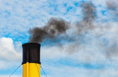 Chimney from steamboat with black coal smoke, yellow and black chimney with cloudy clear sky photo