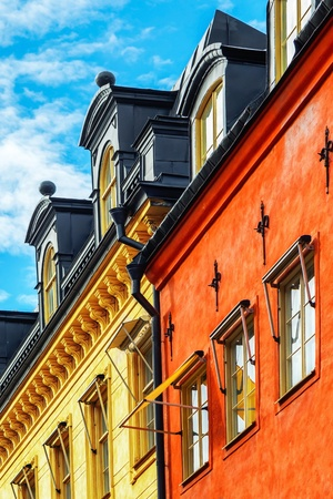 Old red and yellow facade of buildings with windows and blue sky - Stockholm, Sweden Stock Photo - 17597870