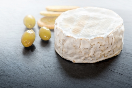 Camembert on grey granite with olives and crackers