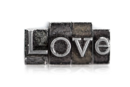 The word  love  in letterpress type on withe background - Macro photo