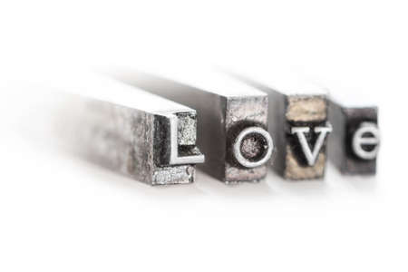 The word  love  in letterpress type on withe background - Macro fom the side photo