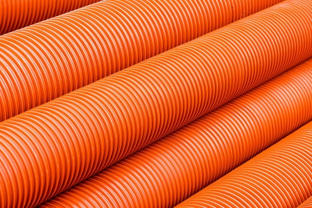 Orange plastic PVC pipes - abstract industrial object concept photo
