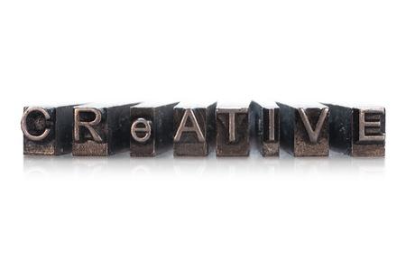 CREATIVE written in metallic letterpress on a white background Stock Photo