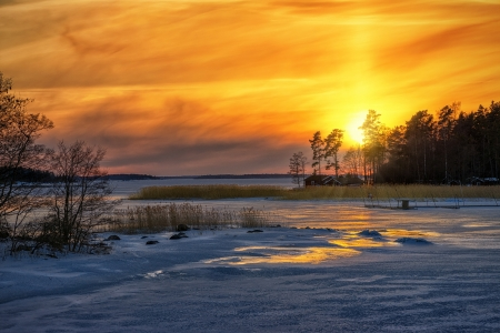 Winter sunset reflections from iced sea with red houses in the distance - Sweden