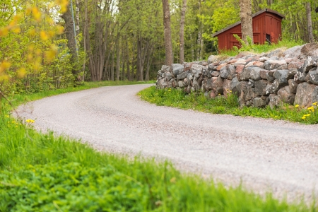 Side of a countryroad with a stonewall and a red house in Sweden during summer
