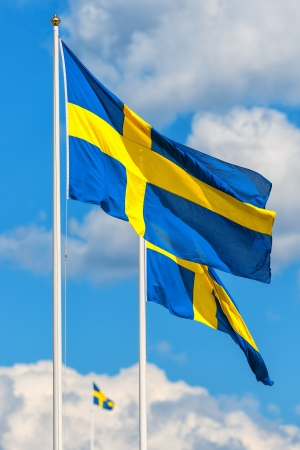 Three Swedish flags with the flag in front in focus on a typical summer sky in Sweden photo
