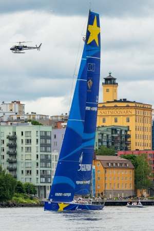 STOCKHOLM - JUNE, 30: Sailboat Esimit Europa 2 departs from Stockholm in the ÅF Offshore Race (Gotland runt) class ORC A, also a news helicopter above the boat and a Seaman in the mast, June 29, in Stockholm, Sweden