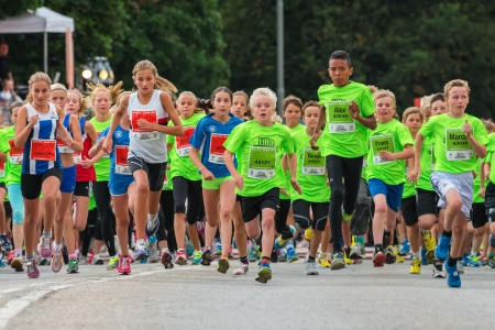 running track: STOCKHOLM - AUG, 17  The children just after the start in the Midnight Run for children  Lilla Midnattsloppet  event, a group of excited children waiting  Aug 17, 2013 in Stockholm, Sweden