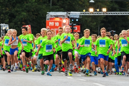 lilla: STOCKHOLM - AUG, 17  The beginning of one of many groups for children in the Midnight Run for children  Lilla Midnattsloppet  event, a group of excited children running  Aug 17, 2013 in Stockholm, Sweden Editorial