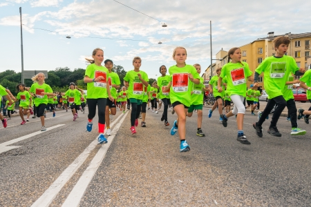 lilla: STOCKHOLM - AUG, 17  Groups for children running by in the Midnight Run for children  Lilla Midnattsloppet  event, a group of excited children running  Aug 17, 2013 in Stockholm, Sweden