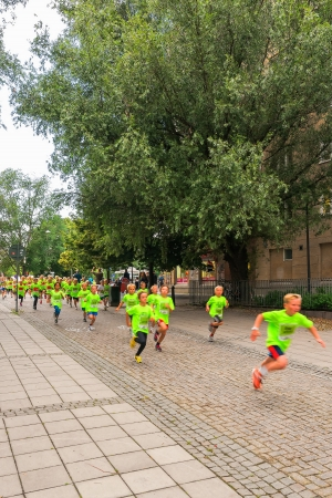 STOCKHOLM - AUG, 17  Competing children in one of many groups for children in the Midnight Run for children  Lilla Midnattsloppet  event, a group of excited children running in a alley  Aug 17, 2013 in Stockholm, Sweden