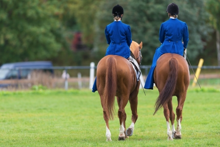 STOCKHOLM - SEP, 22  Two women from the Blue Star riding sidesaddle at the The Mounted Guard event for the public in Ryttarstadion Sep 22, 2013 in Stockholm, Sweden