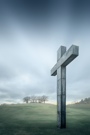 Christian cross against the sky and rolling hills  Religious symbol of Christianity photo
