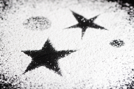 Black star and some planets made with white powdered sugar on a black granite plate Stock Photo