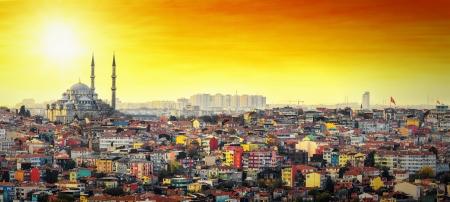 オレンジ色の空とサンセットでカラフルな住宅街でイスタンブール モスク スレイマニエ