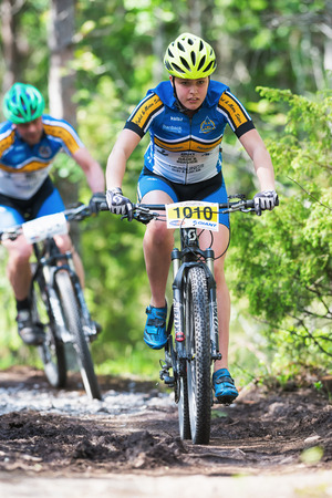 TULLINGE, STOCKHOLM - JUNE 8: Young woman MTB cyclist in forest trail at Lida loop race 2014 during a sunny day in the Swedish nature. June 8, 2014 in Stockholm, Sweden.