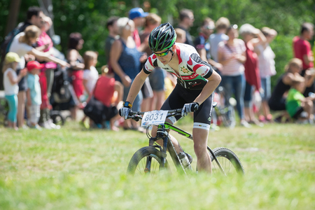 mountainbike: TULLINGE, STOCKHOLM - JUNE 8: Man coming thru the grass in Lidaloop mountainbike race 2014 during a sunny day in the Swedish nature. June 8, 2014 in Stockholm, Sweden.
