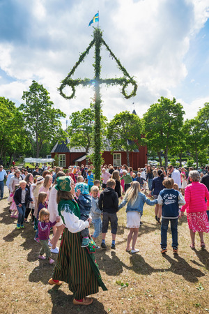 midsummer pole: SINGO, NORRTALJE - JUNE 20: Traditional swedish midsummers day with people dancing around the midsummer pole or maypole. June 20, 2014 in Singo, Sweden.