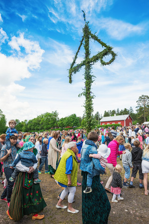 SINGO, NORRTALJE - JUNE 20: Traditional swedish midsummers day with people dancing around the midsummer pole or maypole. June 20, 2014 in Singo, Sweden.