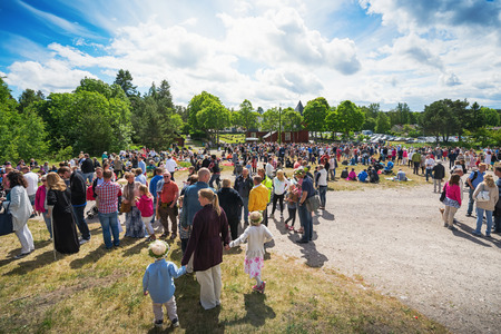 SINGO, NORRTALJE - JUNE 20: People gathered at a traditional swedish midsummer celebration with a maypole in a outdoor venue. June 20, 2014 in Singo, Sweden.