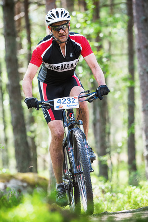 TULLINGE, STOCKHOLM - JUNE 8: Mountain bike cyclist thru the forest at Lida loop race 2014 during a sunny day in the Swedish nature. June 8, 2014 in Stockholm, Sweden.
