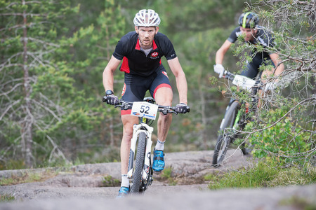 TULLINGE, STOCKHOLM - JUNE 8: MTB cyclist Fredrik Eriksson (later the winner in the race) in the forest during Lida loop race 2014 during a sunny day in the Swedish nature. June 8, 2014 in Stockholm, Sweden.