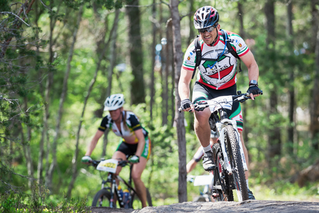 TULLINGE, STOCKHOLM - JUNE 8: Mountain bike cyclist in a uphill forest trail at Lida loop race 2014 during a sunny day in the Swedish nature. June 8, 2014 in Stockholm, Sweden.