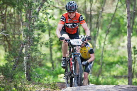 TULLINGE, STOCKHOLM - JUNE 8: Focused mountain bike cyclist in a uphill forest trail at Lida loop race 2014 during a sunny day in the Swedish nature. June 8, 2014 in Stockholm, Sweden.