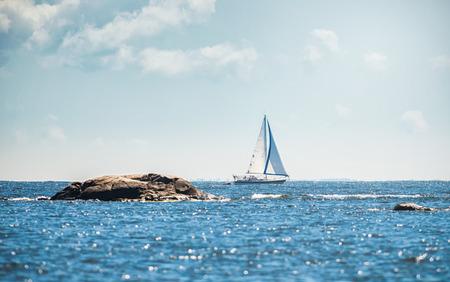 to watersplash: Sailboat cruising thru archipelago with watersplash in the foreground, Sweden Stock Photo