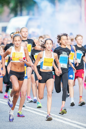 lilla: STOCKHOLM - AUG, 16: Closeup of a group of runners in the Midnight Run for children (Lilla Midnattsloppet) event. Aug 16, 2014 in Stockholm, Sweden