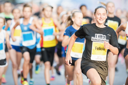 lilla: STOCKHOLM - AUG, 16: Happy girl running by in the Midnight Run for children (Lilla Midnattsloppet) event. Aug 16, 2014 in Stockholm, Sweden