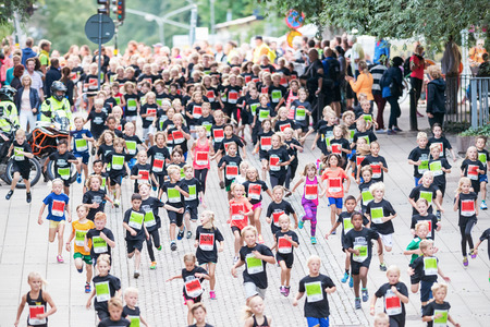 after midnight: STOCKHOLM - AUG, 16: The big group after the first curve of the youngest in the Midnight Run for children (Lilla Midnattsloppet) event cheered on. Aug 16, 2014 in Stockholm, Sweden