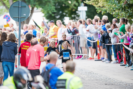 STOCKHOLM - AUG, 16: The leader after the first curve of the youngest in the Midnight Run for children (Lilla Midnattsloppet) event cheered on. Aug 16, 2014 in Stockholm, Sweden