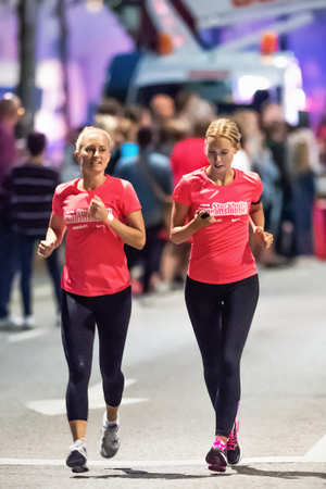 STOCKHOLM - AUG, 16: Two female runners in one of the many groups of the Midnight Run (Midnattsloppet) event. Aug 16, 2014 in Stockholm, Sweden
