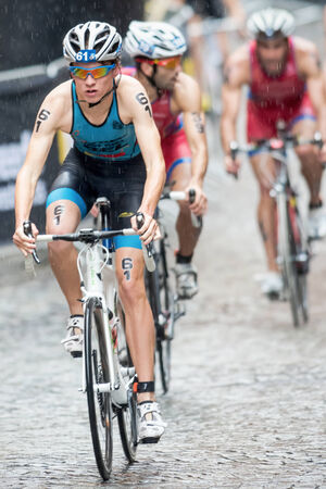 STOCKHOLM - AUG, 23: Triathlete Marten Van Riel cycling in heavy rain at the cobblestone road in the Mens ITU World Triathlon Series event August 23, 2014 in Stockholm, Sweden